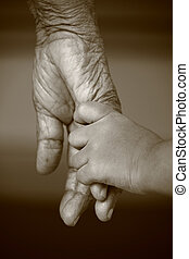 Hands of two generation - Hand of a kid holds the hands of...