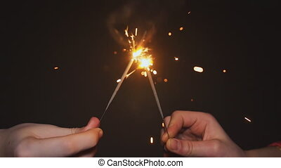 Hands of two girls lit sparklers. Ignition Bengal fire close-up.