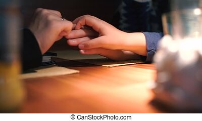 Hands of two lesbians. A daughter takes one hand and takes it.