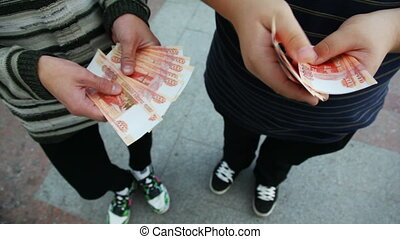 hands of two men believe Russian Ruble front of camera