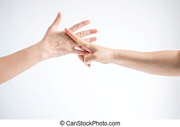 Hands of two people playing rock paper scissors; hands showing shape of scissors symbol and paper symbol; concept of business competition.