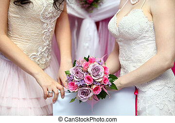 hands of two young brides wearing white dresses hold...