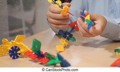 Hands of unknown boy playing with building kit - Close-up of...