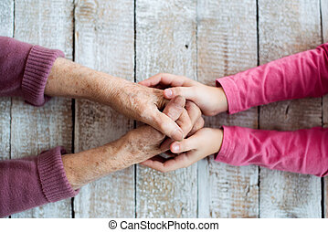Hands of unrecognizable grandmother and her granddaughter - ...