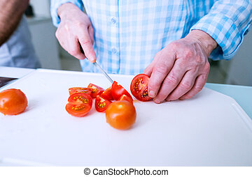 Hands of unrecognizable senior woman cutting tomatoes. Preparing