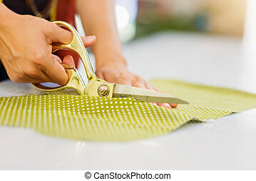 Hands of unrecognizable tailor woman cutting fabric with...