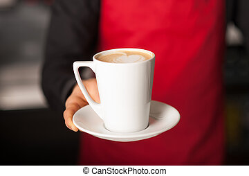 Hands of waiter serving a cup of cappucino - Barista...