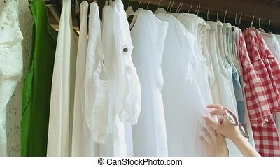 Hands of woman choosing clothes. Girl in clothing shop....