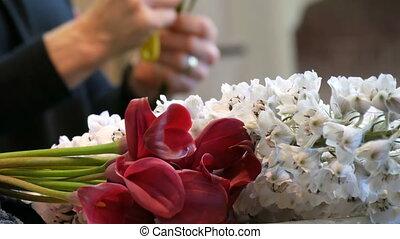 Hands of woman florist making a flower arrangement or a...