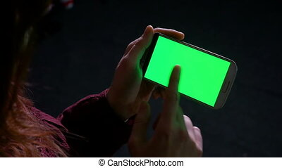 Hands of woman holding a smart phone with green screen and swiping