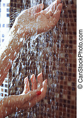 Hands of woman in shower under the flowing water