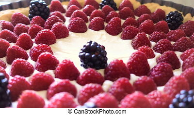 hands of woman making a berry tart with raspberries and...