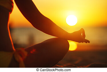 hands of woman meditating in yoga pose at sunset on beach