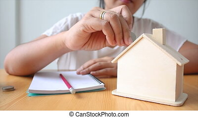 Hands of woman putting coin to House piggy bank saving money for buy home concept