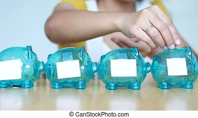 Hands of woman putting money coin into 4 clear piggy bank with blank white paper tag metaphor separate kind of money for spend and saving in difference budget financial concept with ambient sound