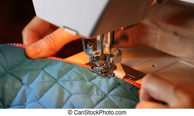 Hands of woman sewing on sewing machine. Zipper repair -...