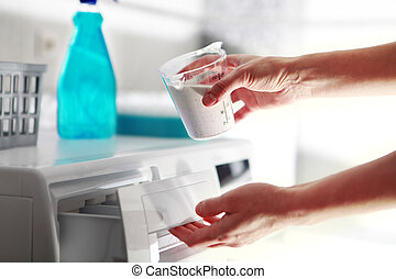 hands of woman that fills detergent in the washing machine