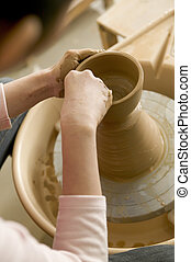 hands of woman turning pottery wheel