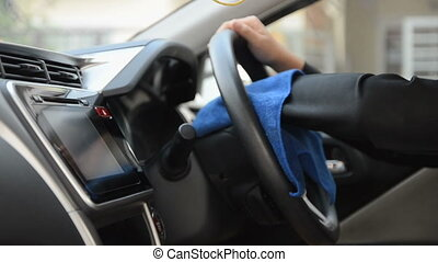 Hands of woman using blue micro fiber fabric to clean up the car