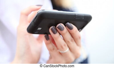 Hands of woman using cell phone