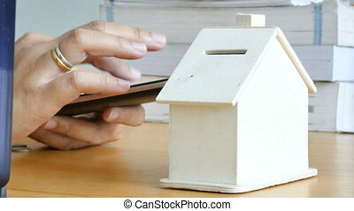 Hands of woman using smart phone computer and putting money coin into piggy bank house metaphor mobile application calculation for saving money for buy home and real estate concept select focus on house