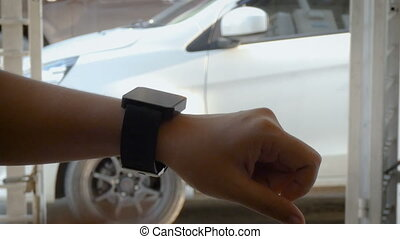 Hands of woman using smart watch to open and close lock and...