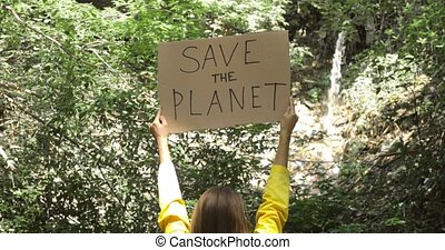 Hands of woman volunteer, ecology fighter near sewage pipe in forest holding banner poster save the planet. Single picket to protect environment. Concept of eco awareness against ecology disaster.