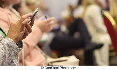 Hands of women with gadgets at business conference