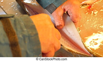 Hands of worker gutting cod, the codfish. A man wearing...