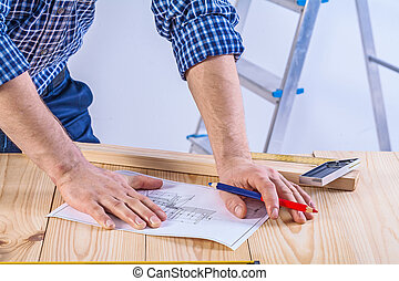 hands of worker on table with blueprint construction concept