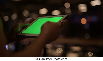 Hands of young Asian man using digital tablet at night