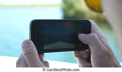 Hands of young boy using smartphone to taking photo of floating boat at beautiful bay at sunny day. Male tourist sailing on ship and enjoying nature landscape during summer travel. Holiday concept
