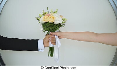 Hands of young couple passing wedding bouquet to each other. Unrecognizable groom giving flowers his beautiful bride. Newlyweds celebrating marriage. Wedding symbol. Slow motion Close up.