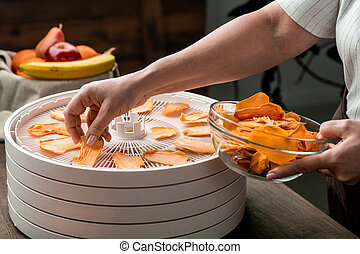 Hands of young housewife putting slices of yellow dried fruits into glass bowl