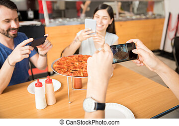 Hands of young man clicking pizza photo using smartphone with friends