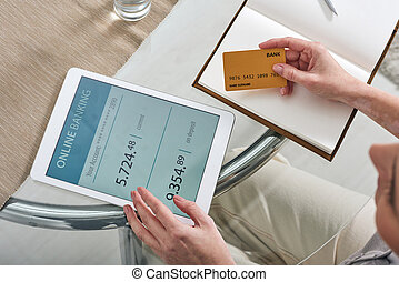 Hands of young mobile woman looking through her online bank account