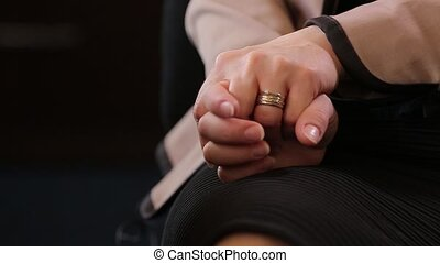 Hands of young nervous woman in session by psychologist....