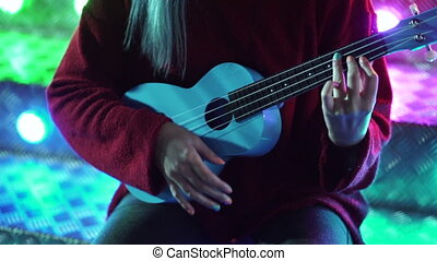 Hands of young pretty girl playing on blue ukulele while sitting on glowing neon stairs in amusement park at night