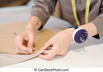 Hands of young seamstress pinning cut sketch to textile