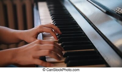 Hands of young teen girl playing on the piano