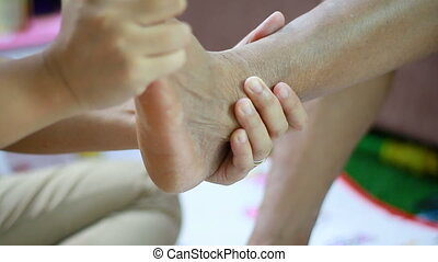 Hands of young woman gently touch massage to foot leg and...