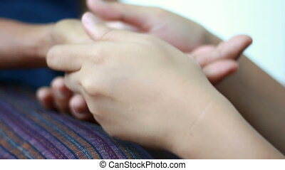 Hands of young woman gently touch massage to Hands of old...