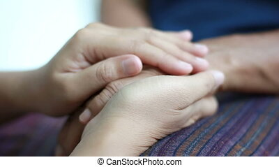 Hands of young woman holding and gentle touch to Hands of...