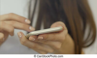 Hands of young woman uses a smartphone