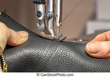 Hands working on a Leather sewing machine in action
