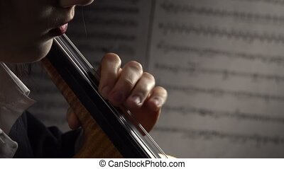 Hands on the cello string in the background sheets with...
