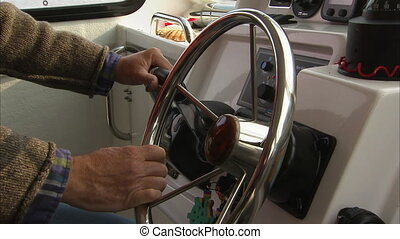 Hands on the steering wheel of a boat