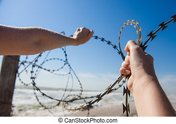 Hands open barbed wire outdoors at beach