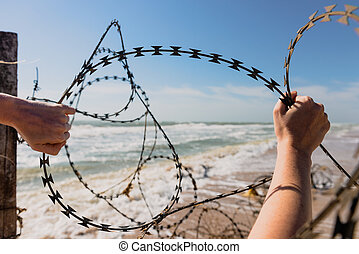 Hands open barbed wire outdoors at beach.