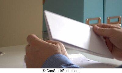 Hands open envelope after receiving subpoena letter - Hands...